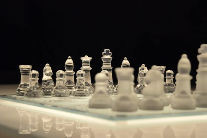glass chess pieces on a chess board